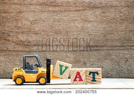 Toy plastic forklift hold block V to compose and fulfill wording VAT on wood background