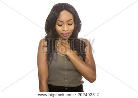 Black female isolated on a white background displaying shy facial expressions. She is young and of African American ethnicity.