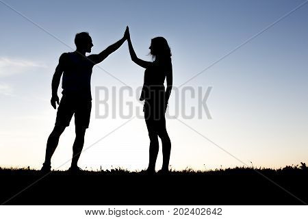 A Happy silhouette couple holding up hands against the sky at dusk