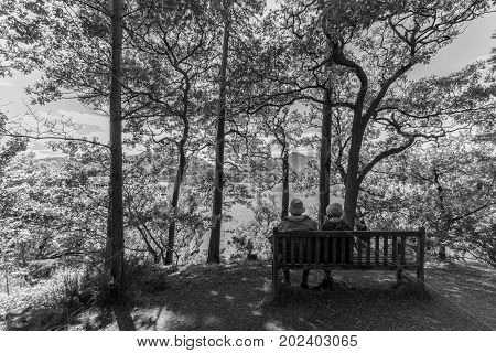 Idyllic scene of old couple seated on bench gazing at Derwent Water lake Keswcik Cumbria UK in black and white