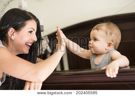 A Mother putting baby to sleep at the crib