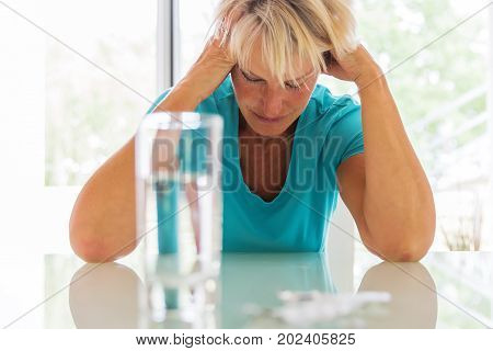 Mature Woman With Headaches Sits In Front Of Water And Pills