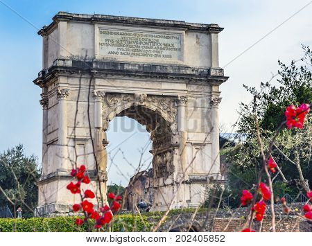 Titus Arch Red Flowers Roman Forum Rome Italy. Stone arch was erected in 81 AD in honor of Emperor Vespasian and his son Titus for conqueiring Jerusalem and destroying the Jewish temple in 70 AD. The Colosseum and the Arch were funded by the riches collec
