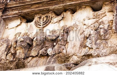 Titus Arch Roman Loot Menorah Temple Jerusalem Forum Rome Italy. Stone arch was erected in 81 AD in honor of Emperor Vespasian and his son Titus for conqueiring Jerusalem and destroying the Jewish temple in 70 AD. The Colosseum and the Arch were funded by