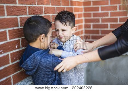 A Teacher Stopping Two Boys Fighting In Playground