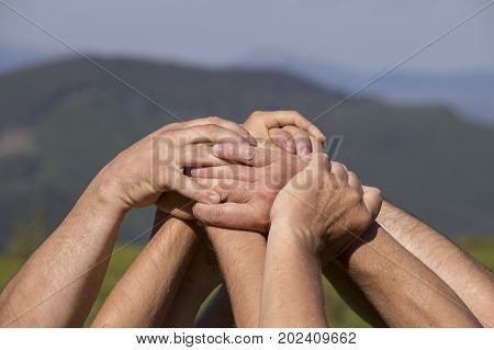 Successful team: many hands holding together on nature background close up