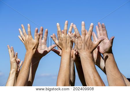 Group raising hands against blue sky background close up