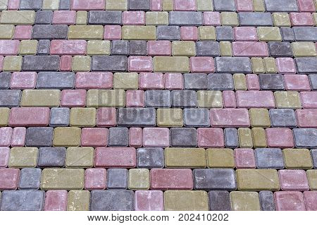 Paving slabs by mosaic close-up. Road paving construction . Fixed tessellated sidewalk tile. Colored concrete paving slab