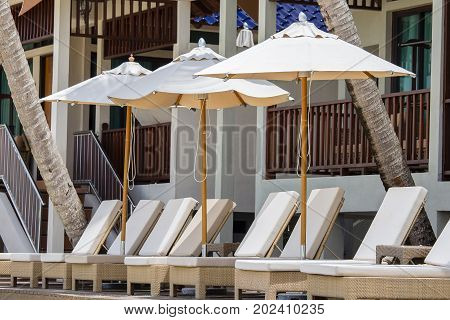 Beach loungers and umbrellas on the beach next to the sea in tropical hotel Thailand
