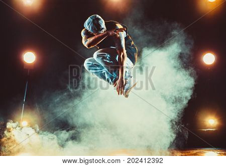 Young man break dancing in club with lights and smoke. Tattoo on body.