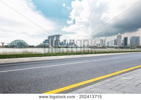 empty asphalt road and cityscape of singapore in blue sky