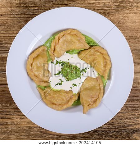 Ukrainian and Russian dish vareniki with mashed potatoes and sour cream and green sauce from spinach and dill in white plate. Close up. Top view