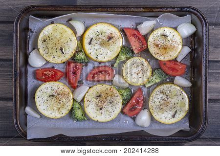 Zucchini tomatoes broccoli and onion watered with olive oil prepared on baking trays for baking in the oven. Top view close up