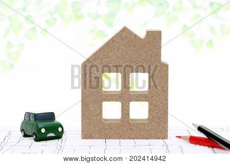 miniature model of house on blueprints on isolated on white background