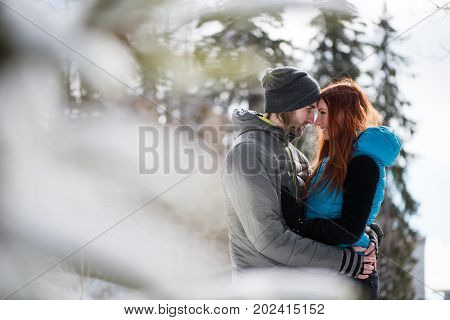 Affectionate young couple hugging outside in winter