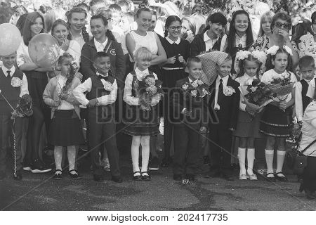 Adygea Russia - September 1 2017: children with bouquets of flowers enrolled in the first class at school at the inauguration of the school year in the day of knowledge a black and white photo