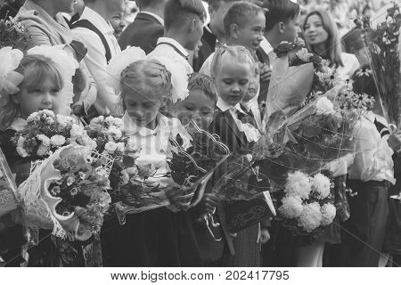 Adygea Russia - September 1 2017: children with bouquets of flowers enrolled in the first class with high school students on the school line in the day of knowledge black and white photo