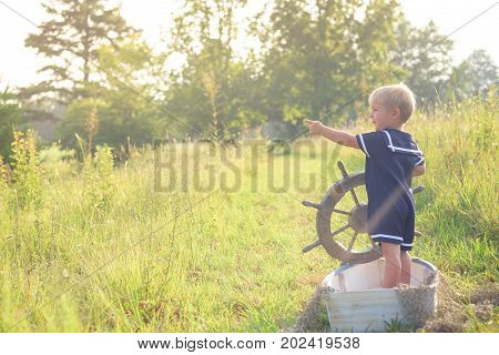 Boy in blue sailor suit playing with steering wheel in the boat, pretending to sail across summer sea of grass, pointing left. Adventure, children activity, game.