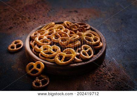 Heap of mini pretzels on wooden plate. Dark style