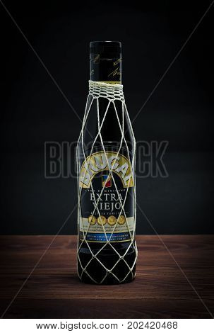 Sankt-Petersburg, Russia - August 30, 2017: Brugal Extra Viejo Rum on wood background. The Brugal Family has been making Rum in Puerto Plato, Dominican Republic for 130 years.