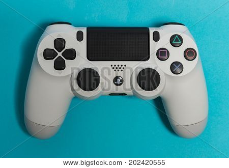 Sankt-Petersburg, Russia - 25 August, 2017: Sony PlayStation 4 game controller on blue background studio shot.