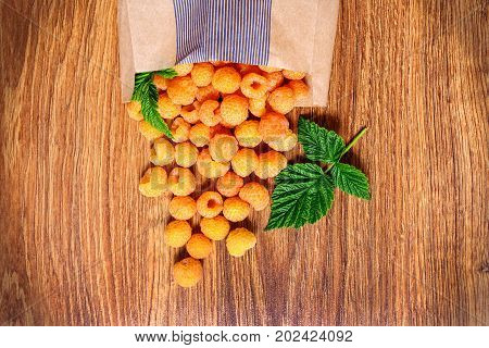 On a wooden table lies a paper bag with scattered yellow raspberries and green leaves.