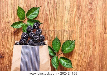 On a wooden table lies a paper bag with scattered large blackberries and green leaves.