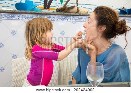 Little Child Feeding Mother At Restaurant