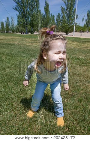 three years old blonde child with pigtail and blue jeans standing and shouting in green grass in public park named Juan Carlos in Madrid Spain Europe