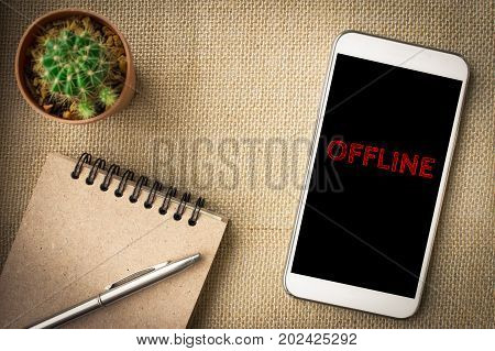 Offline, text message on screen smartphone, brown table with office supplies backdrop background . business concept.