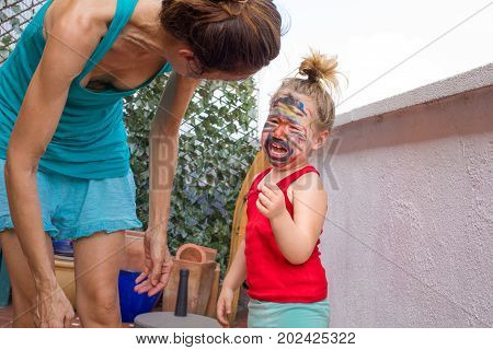 Little Child With Painted Face Screaming Next To Mother