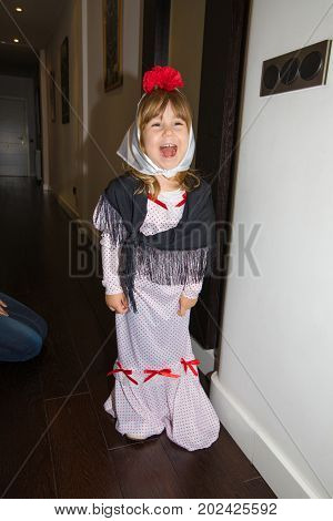 three years old girl disguised as typical and traditional costume of Madrid city in Spain with carnation flower headscarf and dress looking in the mirror smiling for festivity La Paloma