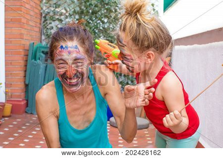 Mother And Daughter With Painted Face Laughing In Terrace