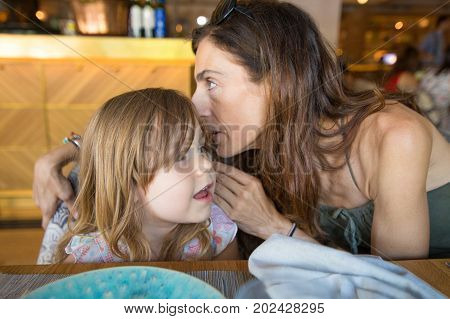 Mother Telling A Secret In The Ear To Girl In Restaurant
