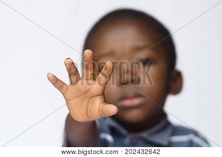African boy holding his hand out as a STOP sign for racism and abuse. Isolated on white. Little African boy making a facial expression. Here he is making a stop sign with his hand.