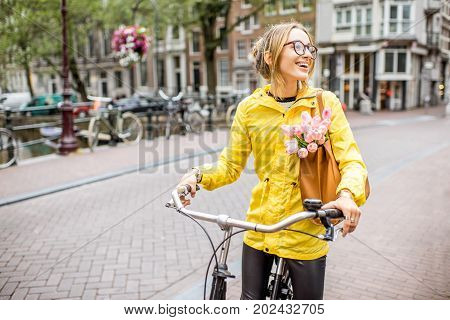 Young woman in yellow raincoat with bag and flowers riding a bicycle in Amsterdam city