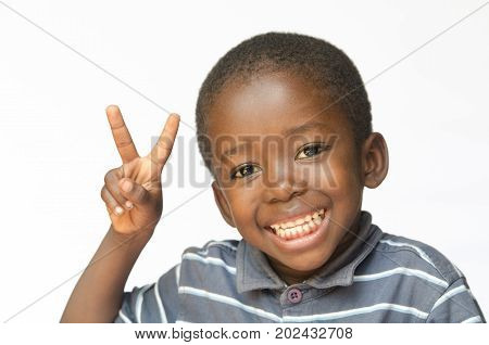 Peace for Africa. Little African boy making a facial expression. Here he is making the classic peace sign with two fingers. Isolated on white.
