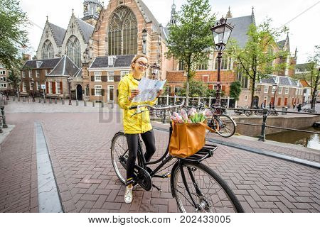 Portrait of a woman tourist in yellow raincoat standing with map and bicycle with Old church on the background in Amsterdam