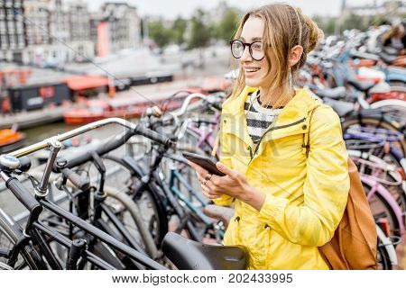 Young woman in yellow raincoat standing with phone on the bicycle multilevel parking in Amsterdam