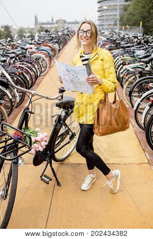 Young woman in yellow raincoat standing with tourist map on the bicycle parking in Amsterdam