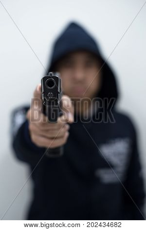 Man criminal pointing gun at the target with one hand on white background selective focus on front gun. Safety and criminal concept background.