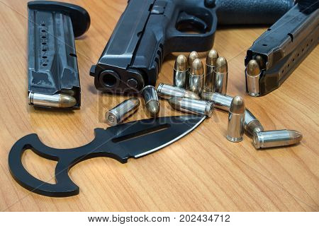 Pistol cartridges bullet and knife on wooden table set of combat weapon concept.