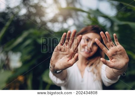 Gardener Showing Her Dirty Palms At Greenhouse