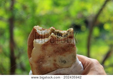 A man holding a traditional Lebanese food breakfast mankousheh.