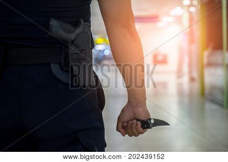 Rear view of man holding a knife in his hand and carry a gun weapon in holstered at the waist.