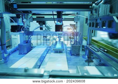 Close up soldering iron tips of automated manufacturing soldering and assembly printed electric circuit board