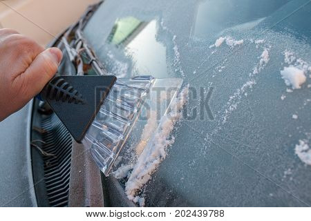scraping ice from the windshield on a cold morning
