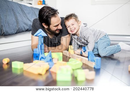 A cute child playing with color toy indoor with his dad