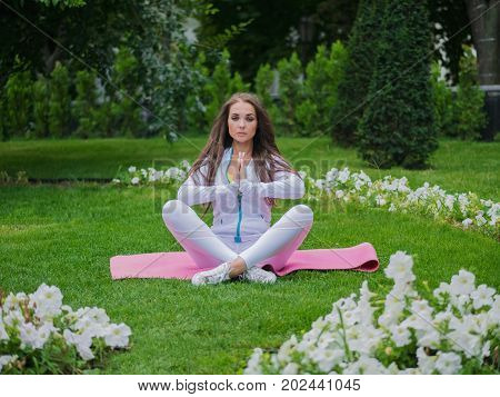 Girl doing yoga pose at the park in the morning. Woman sitting in lotus pose and meditates near flowers in the summer.