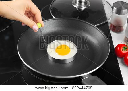 Hand of woman frying sunny side up egg in mold